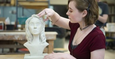 A student uses her hand to mold a sculpture of a face.