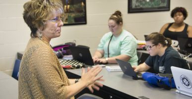 AUM professor Amy Locklear leads a discussion at the front of an English class. .