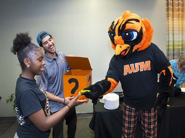 Curtiss in pajamas handing a student an item at Professors and Pajamas event