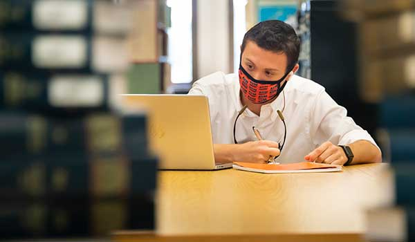 man with mask working on computer